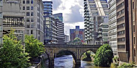 Irwellin joki virtaa Manchesterin modernien asuinrakennusten vieressä.